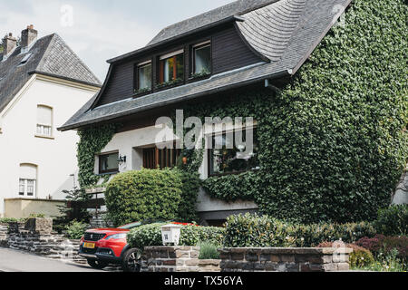 Vianden, Luxembourg - May 18, 2019: Facade of a typical Luxembourgish house covered in green ivy in Vianden, town in Luxembourg's Ardennes region know - Stock Photo