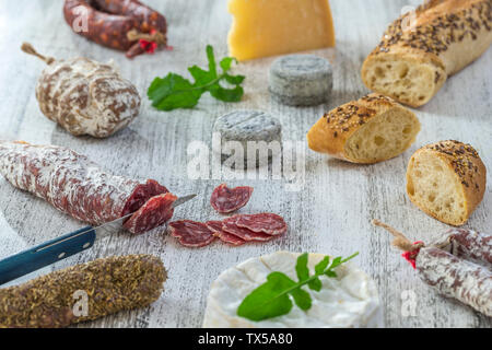 French snacks with wine - various types of cheeses, bread , dry saussages, charcuterie, red vine on a gray background. Top view. Food background - Stock Photo