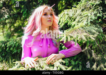 Fairy girl unicorn with rainbow hair and shiny makeup in summer forest standing between pine trees. - Stock Photo