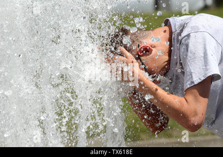 Berlin, Germany. 24th June, 2019. At temperatures around 29 degrees Celsius a young man refreshes himself in the Berlin pleasure garden at the water of a well. Temperatures are expected to rise further in the coming days. Credit: Wolfgang Kumm/dpa/Alamy Live News - Stock Photo