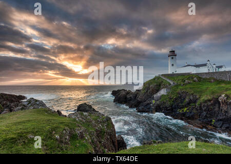 Sunrise over the Atlantic Ocean and Fanad Head Lighthouse in County Donegal Ireland - Stock Photo