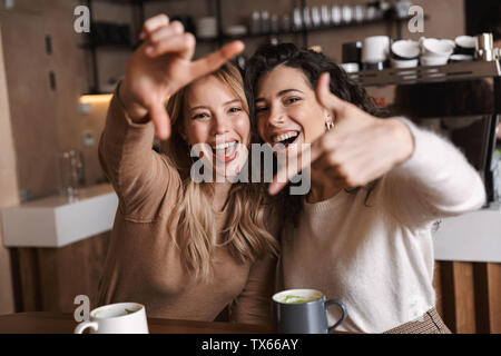 Two cheerful young girls friends sitting at the cafe table, having fun together, drinking coffee - Stock Photo