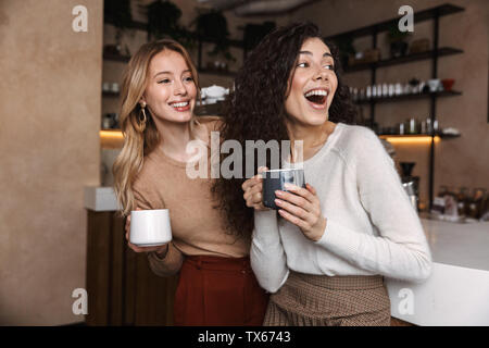 Two cheerful young girls friends standing at the cafe counter, having fun together, drinking coffee - Stock Photo