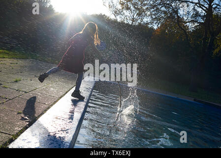 Full length shot of a young girl splashing water with a tree branch in the pool in spring sunshine - Stock Photo