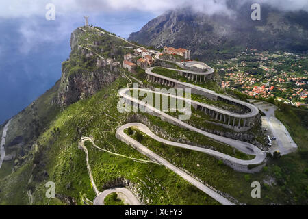 Magnificent sunny cityscape of Maratea hill-town on Tyrrhenian coast in Italy. There is a serpentine roadway to a top of a hill with a big statue of J - Stock Photo