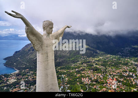 Incredible large monument of Jesus with outstretched hands on the sea background in Maratea hill-town on Tyrrhenian coast in Italy. Aerial horizontal - Stock Photo