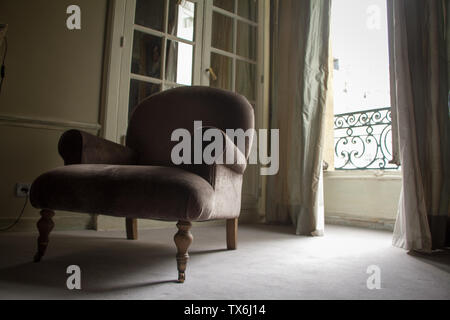 Paris, France - July 05, 2018: Bottom view of an elegant gray armchair over a window with shutters in a historic apartment on Place Vendome in Paris - Stock Photo