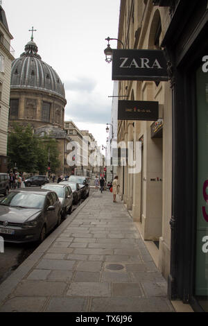 Paris, France - July 05, 2018: Narrow cobblestone street in the center with signs of fashionable boutiques against the backdrop of an old Catholic cat - Stock Photo