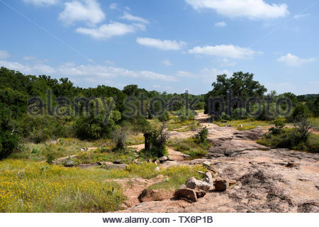 The end of the trail. Base of Summit Trail at Enchanted Rock looking back towards parking lot, gazebo and park office. Returning from hike. Texas USA - Stock Photo