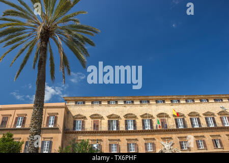 Front side of historic royal palace in Palermo Sicily, royal palace and residence of old kings with beautiful palm - Stock Photo