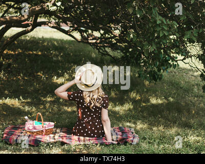 Picnic on summer vacation Photo with copy space A young blonde girl in a straw hat is resting in the garden on a sunny day Back view - Stock Photo