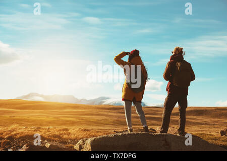 Two backpackers or travelers stands on big rock and looks at mountains - Stock Photo