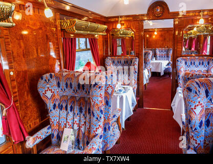 Interior of a panelled dining car Ione with tables set for lunch in the Belmond Venice Simplon Orient Express - Stock Photo