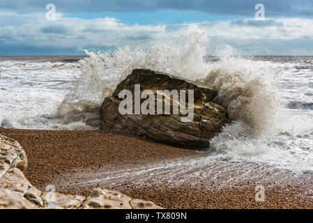 Waves crashing against the rocks during a winter storm on a Dorset beach - Stock Photo