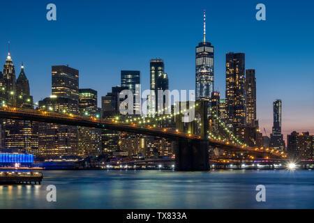 The Brooklyn Bridge, East River and Manhattan skyline at night, New York, USA - Stock Photo