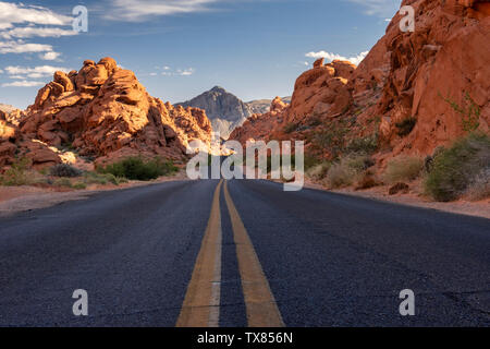 Evening light illuminates the Highway through the Valley of Fire State Park, Nevada, USA - Stock Photo