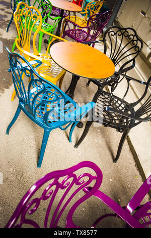 Empty vintage terrace in historical downtown with multi-colored chairs on the pavement sidewalk. Colorful chairs in retro atmosphere at cafe bar outdo - Stock Photo