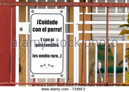 Cuban humor on a sign of a house porch. It reads 'Beware of Dog and of the Cat as well, it is a weird animal'. Houses in some neighborhoods are heavil - Stock Photo