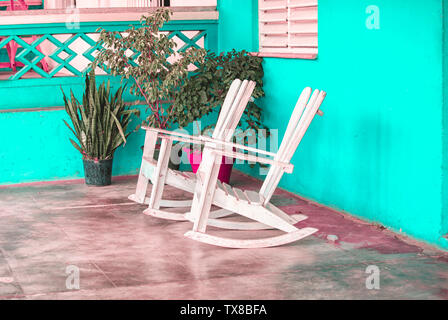 Two wooden rocking chairs on a porch in the Caribbean - Stock Photo