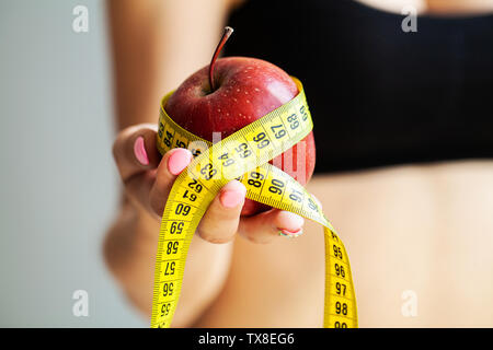 Diet concept. Apple with measure tape in female hand - Stock Photo