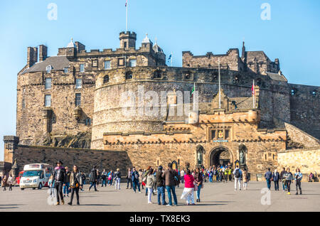 Wide view of visitors on the esplanade, with others going in an out of the main front entrance to Edinburgh Castle, Scotland, UK. - Stock Photo