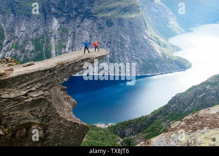 Trolltunga is the most spectacular scenic cliff in Norway. Couple of tourists is standing on a rock - Stock Photo