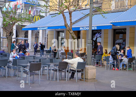 April 18, 2019 : People sitting and enjoying meals purchased at McDonald's restaurant in the city centre square - Stock Photo