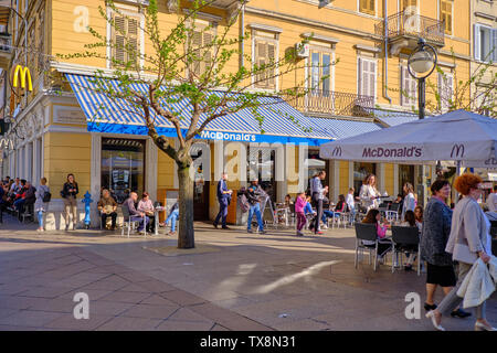 April 19, 2019 : People sitting and enjoying meals purchased at McDonald's restaurant in the city centre square - Stock Photo