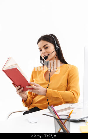 Portrait of caucasian hotline assistant woman wearing microphone headset reading book while working in office - Stock Photo