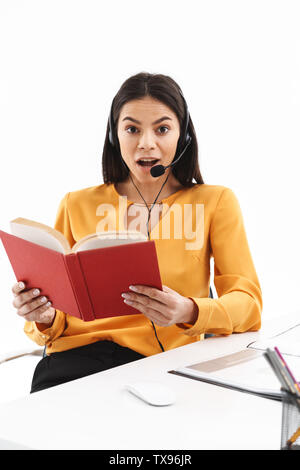 Portrait of attractive hotline assistant woman wearing microphone headset reading book while working in office - Stock Photo