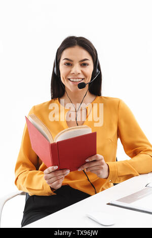 Portrait of happy hotline assistant woman wearing microphone headset reading book while working in office - Stock Photo