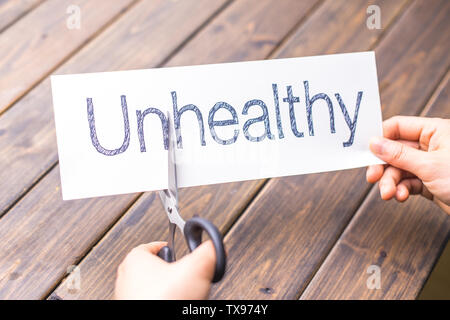 woman cuts un from word unhealthy on white paper - Stock Photo
