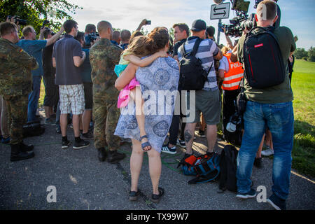 Jabel, Germany. 24th June, 2019. A resident of Jabel with a child in her arms follows the press release of the Federal Minister of Defence near the crash site of a Eurofighter. On Monday, the German Air Force confirmed the crash of two 'Eurofighters' in Mecklenburg-Western Pomerania after a collision in the air. Both pilots could operate the ejection seat, but one of the two soldiers could only be rescued dead. Credit: Jens Büttner/dpa-Zentralbild/dpa/Alamy Live News - Stock Photo