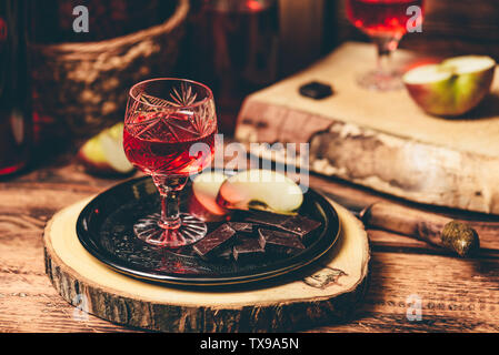 Glass of homemade currant nalivka and chocolate with sliced apple on metal tray - Stock Photo