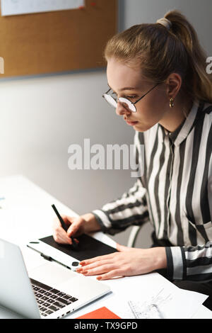 Photo of blonde european woman architect wearing glasses designing draft on graphic tablet computer and sitting at workplace in office - Stock Photo