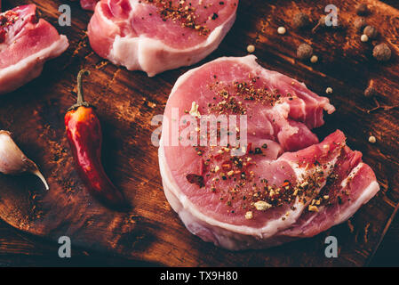 Pork loin steak with different spices on chopping board - Stock Photo