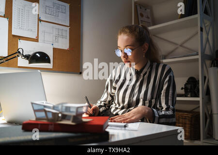 Photo of focused cute woman architect wearing glasses designing draft on graphic tablet computer and sitting at workplace in office - Stock Photo