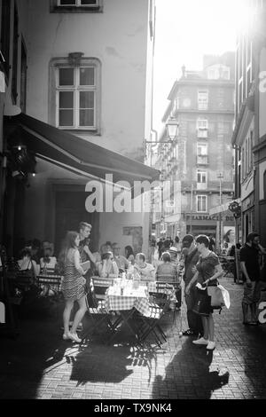 Strasbourg, France - July 22, 2017: Large group of people on outdoor restaurant cafe terrace on 6 Rue du Vieux Seigle eating at L'Epicerie with sunlight flare right corner - black and white