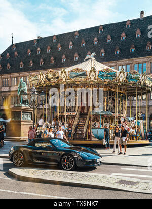 Strasbourg, France - July 22, 2017: Large group of people having fun at the merry-go-round carouse and luxury Porsche 911 supercar in Place Gutenberg, Alsace - Stock Photo