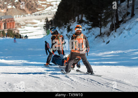 Rescuers at a ski resort evacuate the victim from the slope. Two lifeguards descend a tourist on a special sled on a sunny winter day. Blurred backgro - Stock Photo