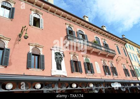 Verona/Italy - May 9, 2015: Pink painted ancient building of renaissance style of XV cetury of Società per il turismo e viaggi Valpantena of Verona. - Stock Photo