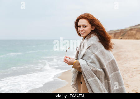 Beautiful young redheaded woman wearing coat, covered in blanket walking at the beach - Stock Photo