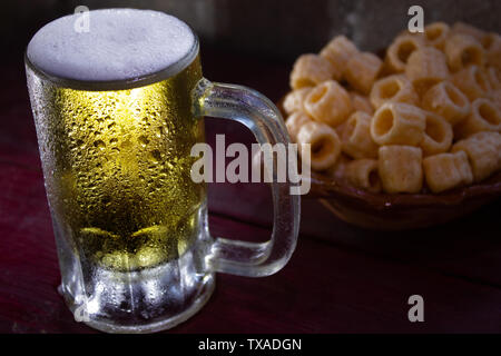 a frozen beer mug with foam on a red wood table with fried snacks - Stock Photo