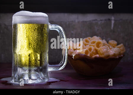 a frozen beer mug with foam pouring on a red wood table with fried snacks - Stock Photo