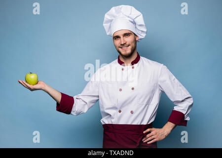 Food service, organic food, healthy diet, cooking and professional culinary concept - chef in white uniform holds vegetables. - Stock Photo