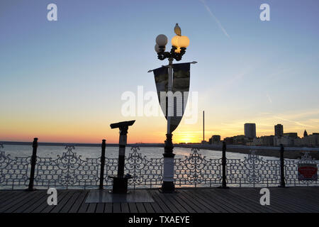 Brighton/UK - August 15, 2016: Beautiful panoramic cityscape of Brighton at sunset viewed from the modern pier of the city decorated with lamp. - Stock Photo