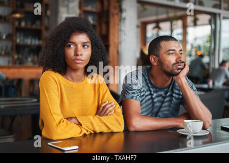 Sad and angry young couple in café - Stock Photo