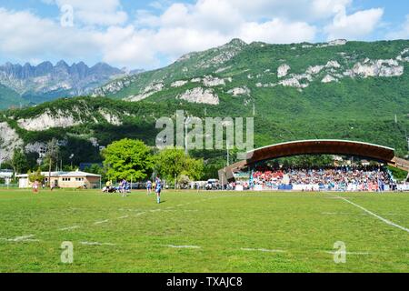 Lecco/Italy - May 24, 2015: Mountain Resegone over Lecco and the rugby match between Rugby Lecco and ASD Rugby Casale on the sports field Lecco Bione. - Stock Photo