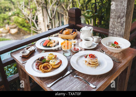 Traditional breakfast with eggs benedict and strawberry pancakes on wooden table on terrace. Fruit plate and cup of coffee - Stock Photo