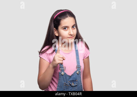 Portrait of serious beautiful brunette young girl in casual style, pink t-shirt and blue denim overalls standing, looking and warning at camera. indoo - Stock Photo